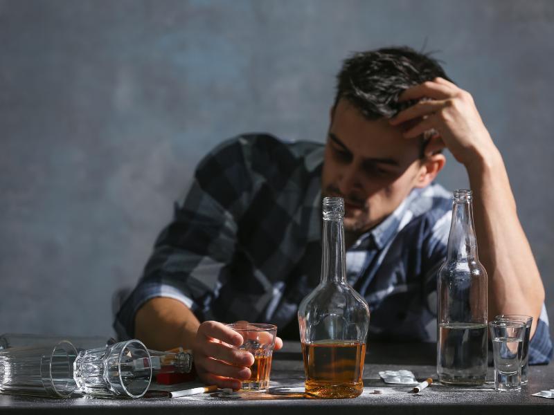 Мужчина пьет дома алкоголь